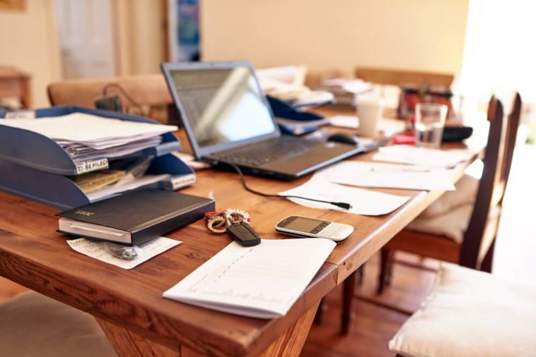 Still life images of a busy entrepreneur's desk in their home office space, with technology and paperwork cluttering the table space