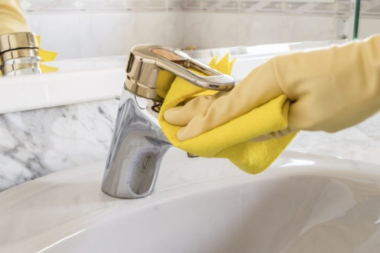 cleaning tap with yellow gloves