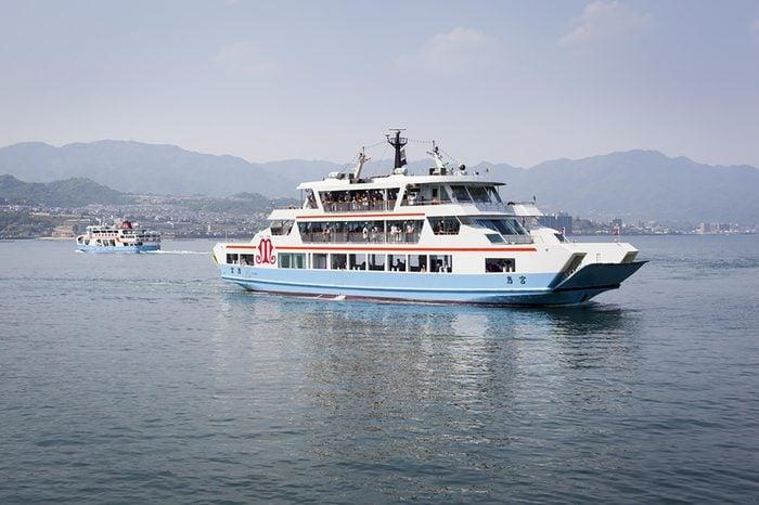 MIYAJIMA, JAPAN - MAY 5: Matsudai Kisen ferries crossing the inland sea between Miyajimaguchi and Miyajima on 5th May 2012. The Ferries carry visitors to the Itsukushima Shrine on Itsukushima island.