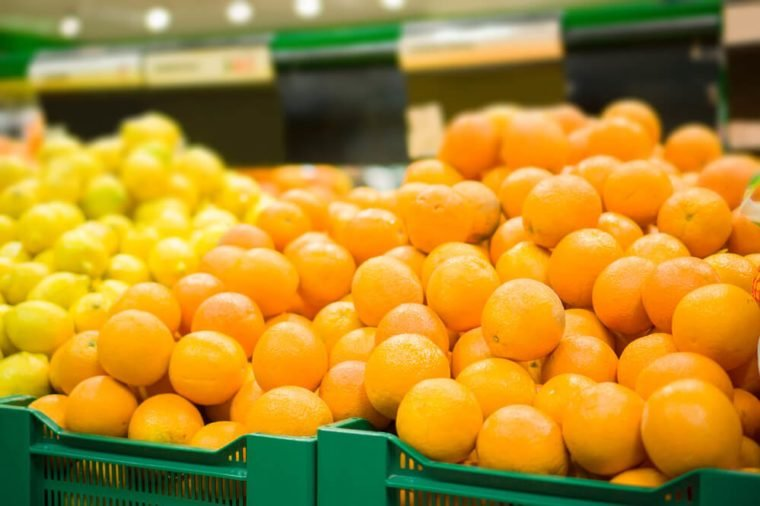 Bunch of oranges and lemons on boxes in supermarket