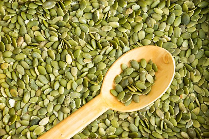 Full frame background texture of fresh cleaned green pumpkin seeds with a rustic wooden spoon arranged diagonally on the surface for use in salads or as a tasty snack