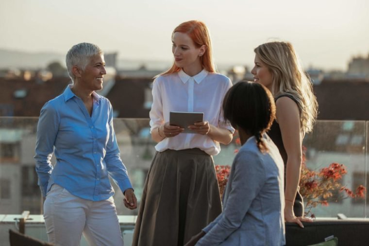 Group of business women using tablet outdoors.