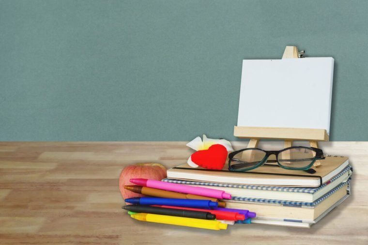 School, education, teacher's day and literacy concept with student and teacher stationery and supples on wood table over grey wall background