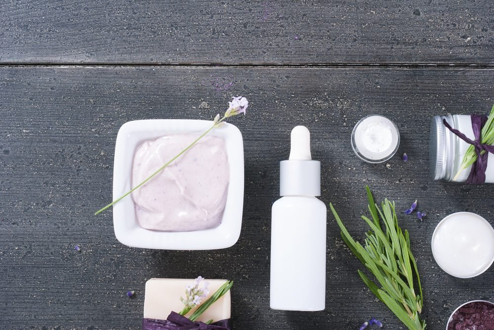 different cosmetic creams, bath salt, soap, anti aging serum pipette with fresh lavender flowers on black wooden texture