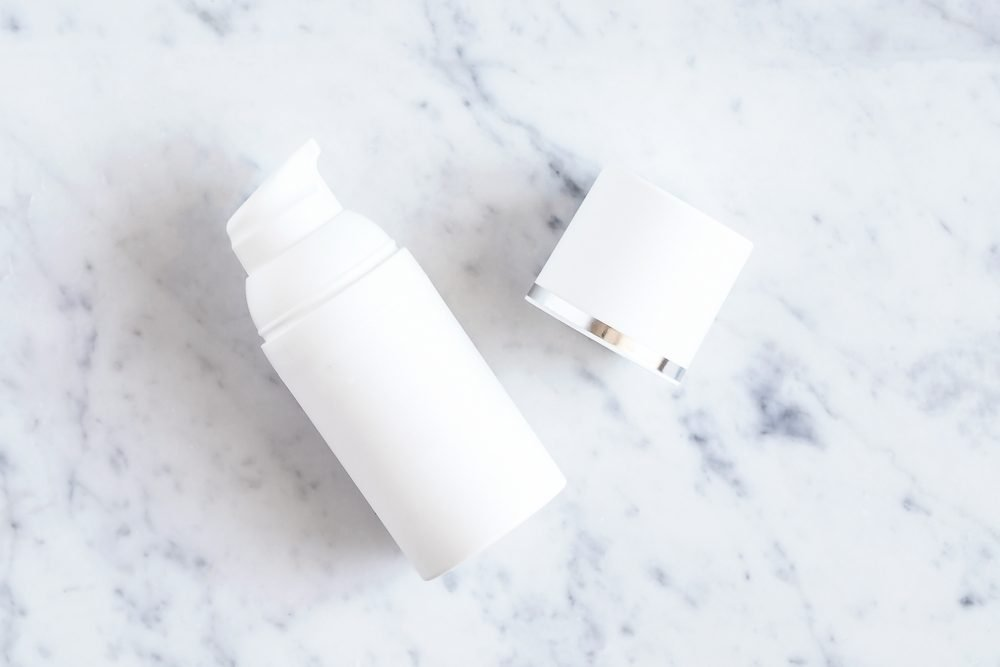 Flat lay with white bottle of cosmetic product on white marble table. Cream, cleancer, moisturizer, lotion. Branding mock up.