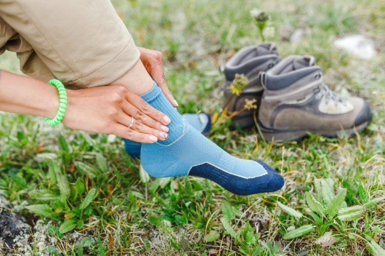 woman puts on high-tech trekking socks for hikes