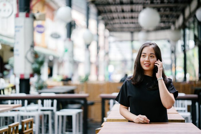 A young and attractive Chinese Asian woman is smiling while she's talking on her smartphone in a city in Singapore, Asia.