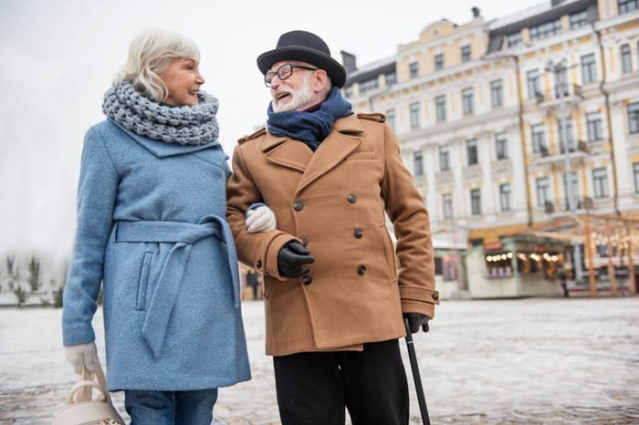 Cheerful old married couple walking arm in arm outdoor in the winter. They are talking and laughing