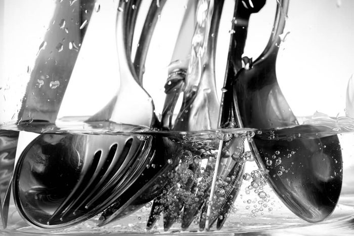 detail of the washing of cutlery under a jet of water and soap