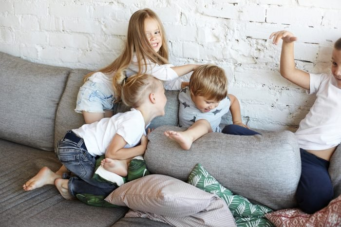 Action shot of four naughty children siblings fooling around at home, turning living room upside down. Restless cheerful kids in casual clothes playing, having fun, fighting with pillows on sofa