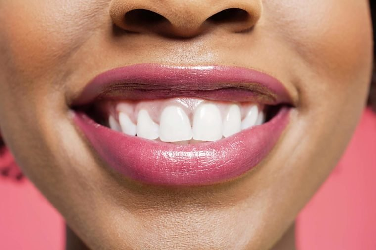 Close-up detail of an African American woman smiling over colored background