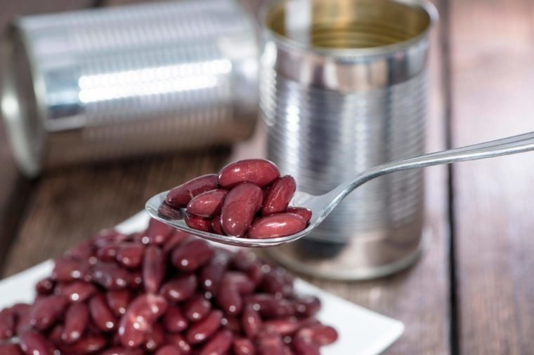 Kidney Beans on a Spoon with blurred cans in the background
