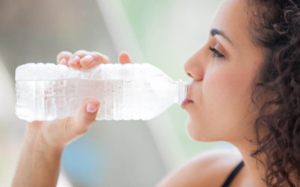 Pretty young woman drinking a bottle of ice cold water