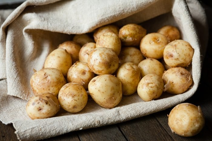 new potatoes with the peel on the table in a bag, food close up