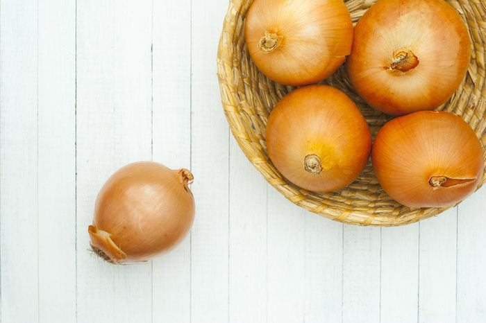 red onions in rustic bowl, white wood table background