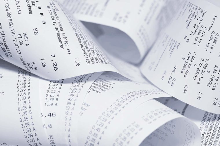 Paper cash register receipts in a lose pile close up