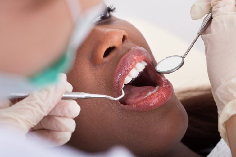 High angle view of female patient being examined by dentist in clinic