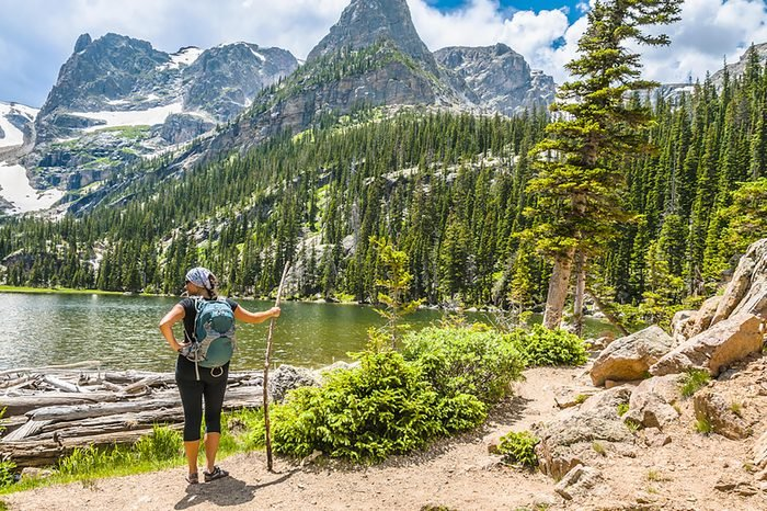 Young attractive female enjoying stunning view at lake Odessa with notchtop peak in rocky mountain national park colorado