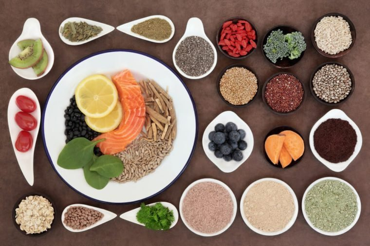 Large health food selection in bowls over lokta paper background.
