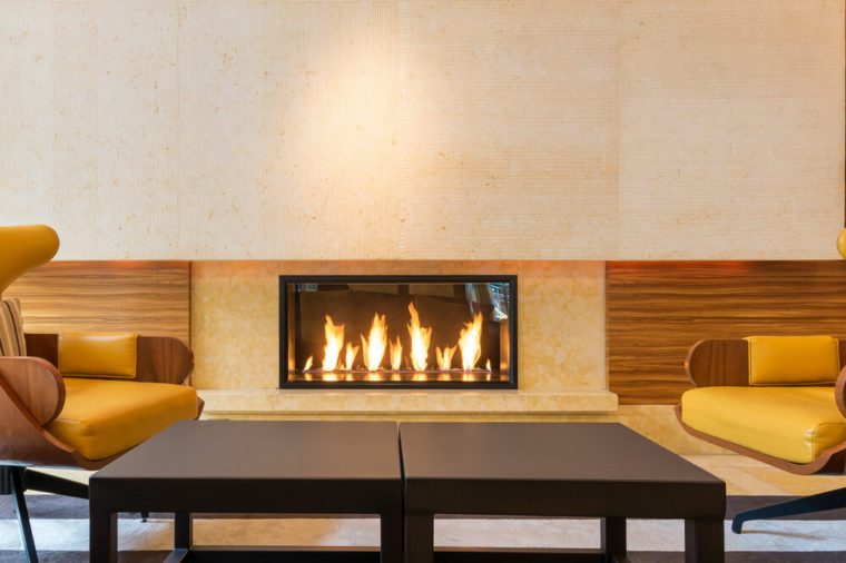 Modern fireplace sitting area with two leather chairs. Interior design.