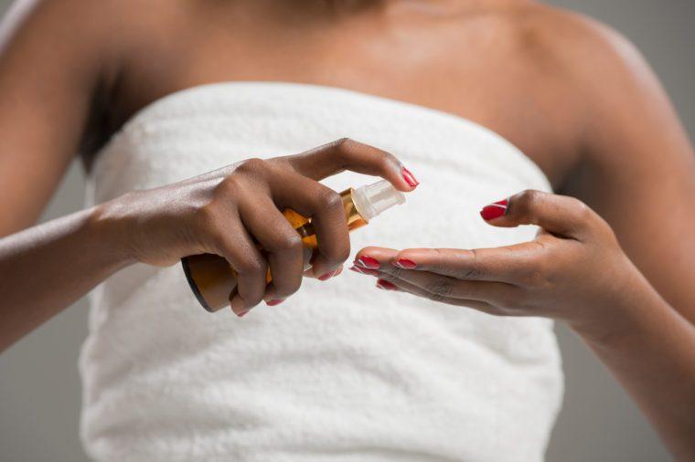 Unrecognizable african woman applying cream . Skincare concept