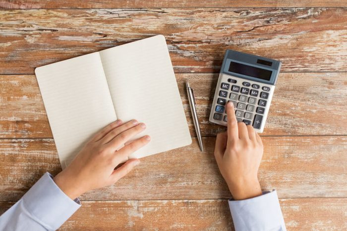 business, education, people and technology concept - close up of female hands with calculator, pen and notebook on table
