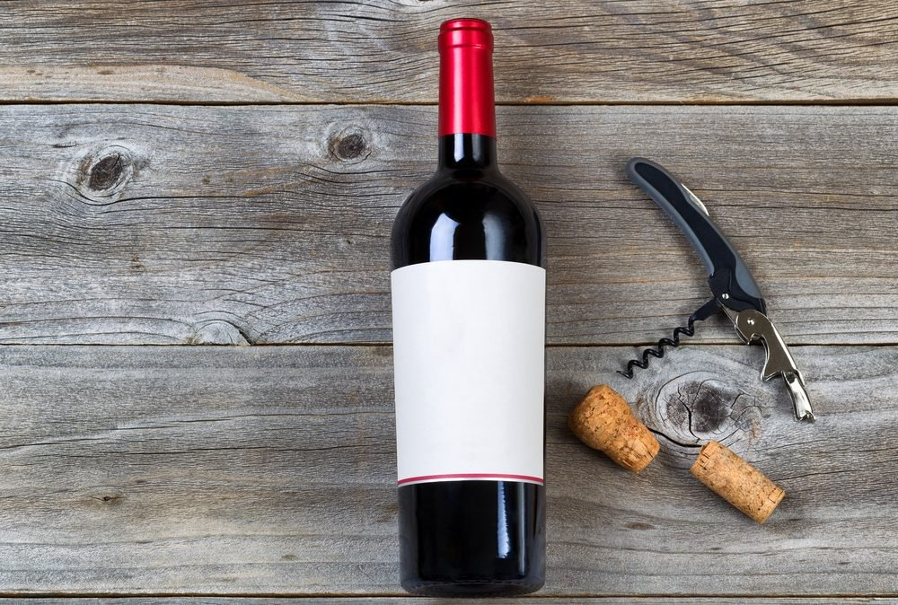 Top view angled shot of red wine bottle with corks and opener on rustic wooden boards