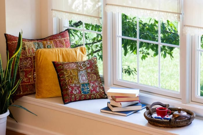 Cup of Coffee on a Tray, Piled Books and Square Pillows at the Reading Corner Inside the House.