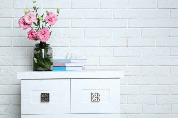 Beautiful flowers with books on brick wall background