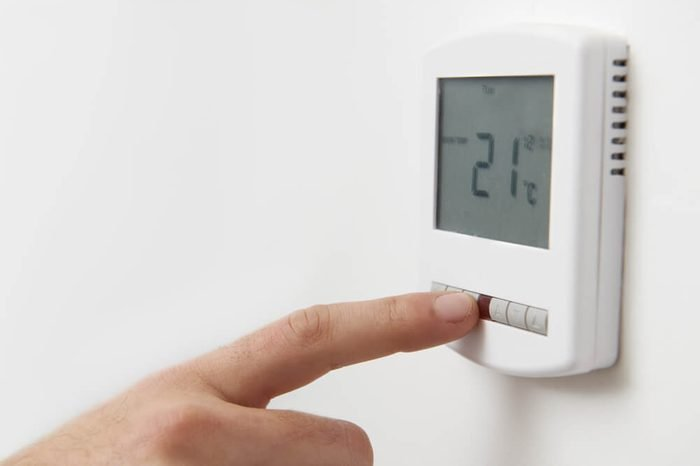 Close Up Of Hand Adjusting Digital Central Heating Thermostat Co