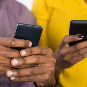 Close-up Of African Couple Holding Mobile Phones In Hand