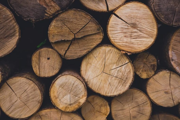 Natural wooden background - closeup of chopped firewood. Firewood stacked and prepared for winter Pile of wood logs