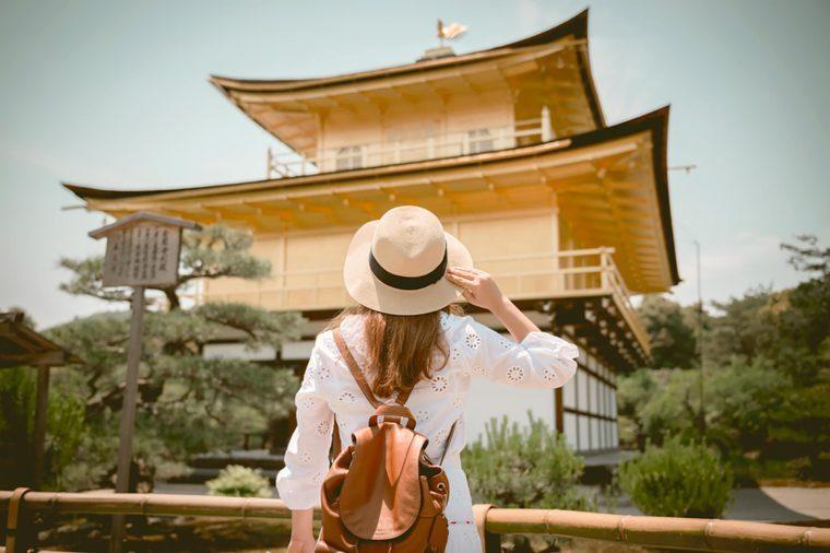 Lady tourist is watching Kinkaku-ji temple in Kyoto, Japan