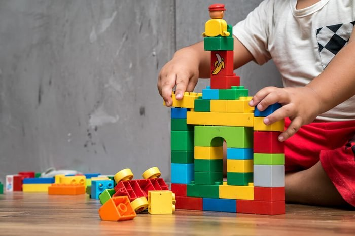 Asian kid boy building house from plastic blocks