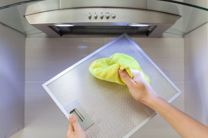 Woman Cleaning Cooker Hood With Rag In Kitchen At Home