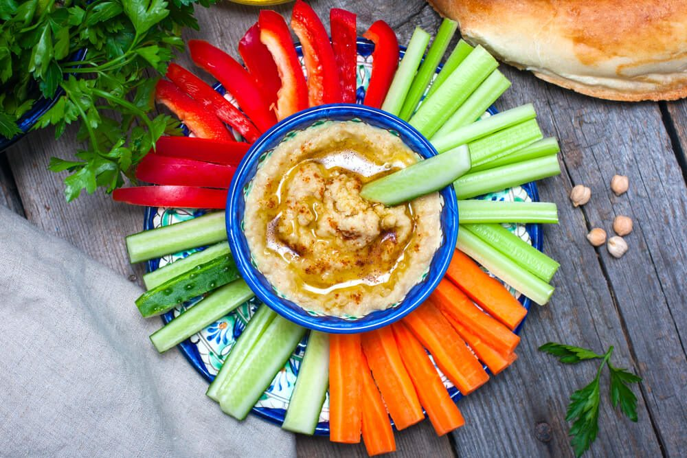 Homemade hummus with fresh vegetables, top view