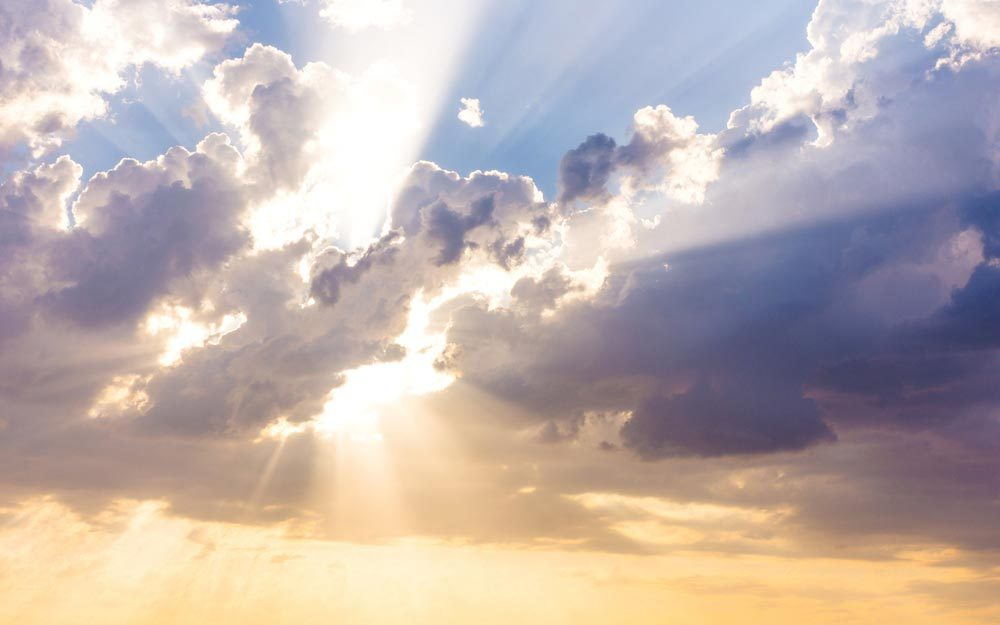 Sun beams or rays breaking through the dark clouds at sunset. Hope, prayer, God's mercy and grace. Beautiful spectacular conceptual meditation background.