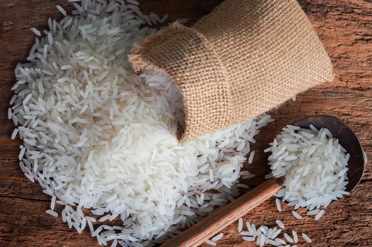 White uncooked Thailand jasmine rice in small burlap bag with wooden spoon on wood table.