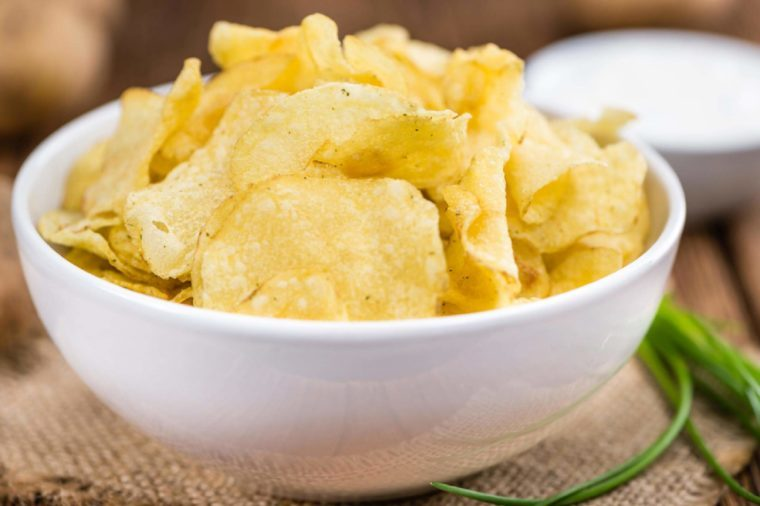 Potato Chips (Sour Cream taste) on a vintage background as detailed close-up shot (selective focus)