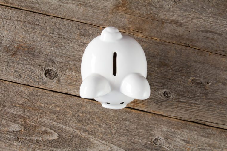 White piggy-bank on the old wooden background. Top view.
