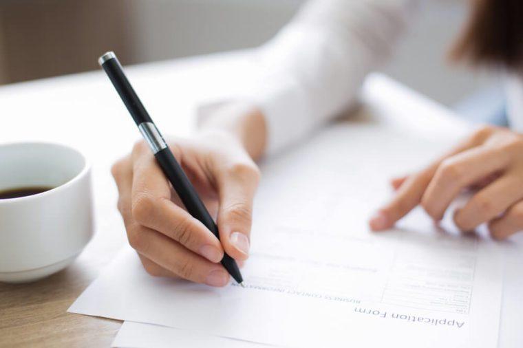 Closeup of Applicant Completing Application Form