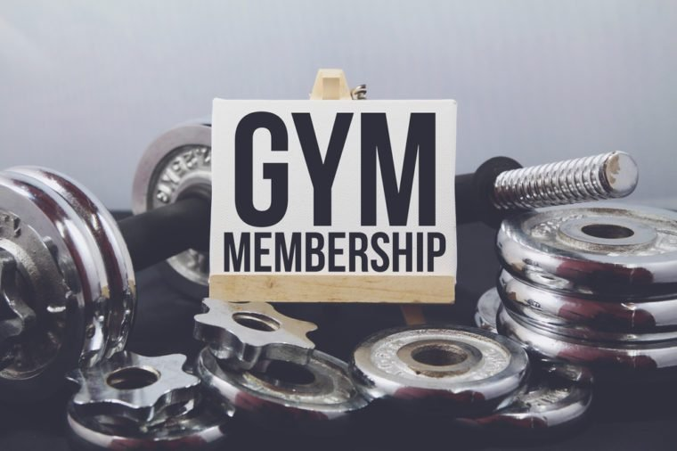 A Concept image of Fitness or bodybuilding background with a dumbbell and extra plates. Vintage tone and a wooden stand with a white frame and a word Gym Membership