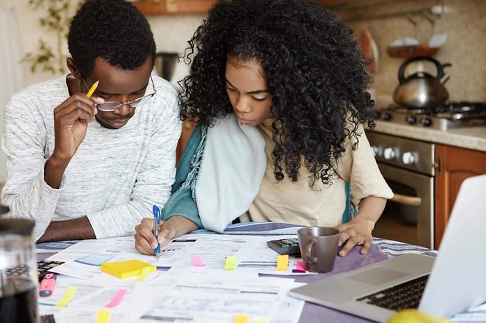 Young confident African housewife with Afro hairstyle helping her husband to manage domestic finances, calculating and making notes with pen, both sitting at kitchen table with laptop and papers