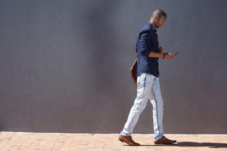 Seitenporträt des afrikanischen männlichen Studenten, der mit Tablette geht