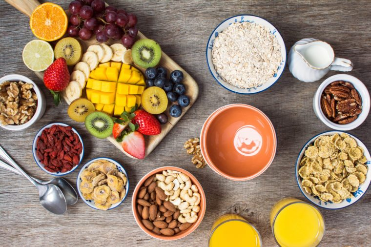 Healthy and various morning breakfast selection: cereals, nuts, orange juice, fruits, berries, selective focus. Top view