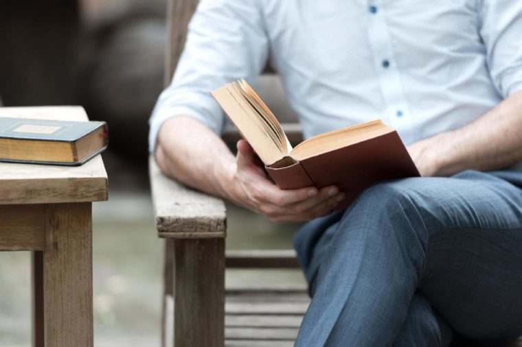 Close up of a man reading a book on a chair in the park, successful people read in the morning every day.