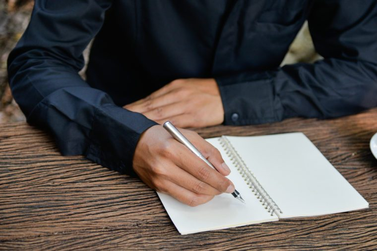 Business concept: Businessman writing on blank notebook. Holding pen in right hand.