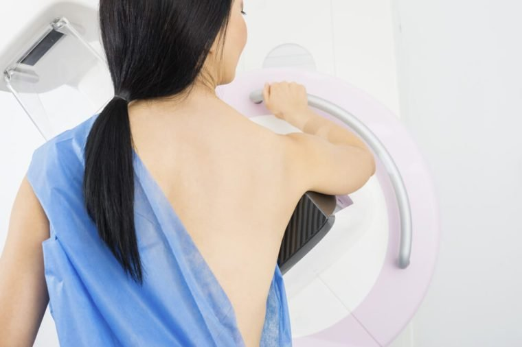 Woman Standing In Front Of Mammography Machine