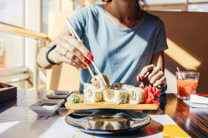 Woman in the blue shirt is eating at a sushi restaurant in summer, close-up