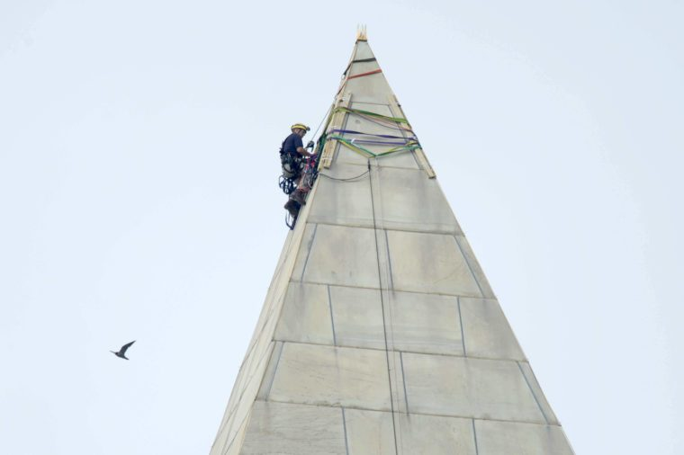 attaches ropes to the top of the Washington Monument